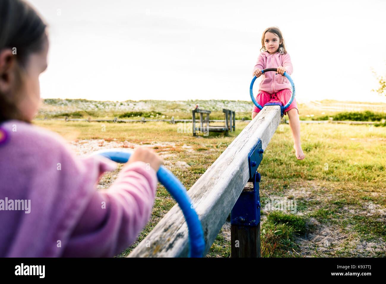 Poco due gemelle bambini stanno cavalcando altalena altalena nel parco. attivo dei bambini che giocano su teeter Immagini Stock