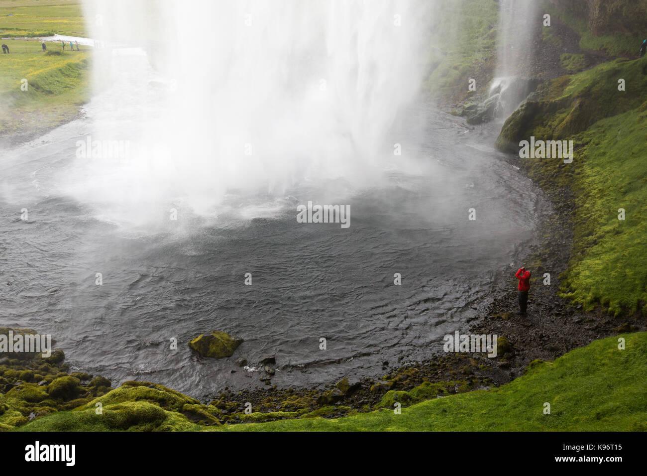 Una donna fotografie sotto Seljalandsfoss cascata. Immagini Stock