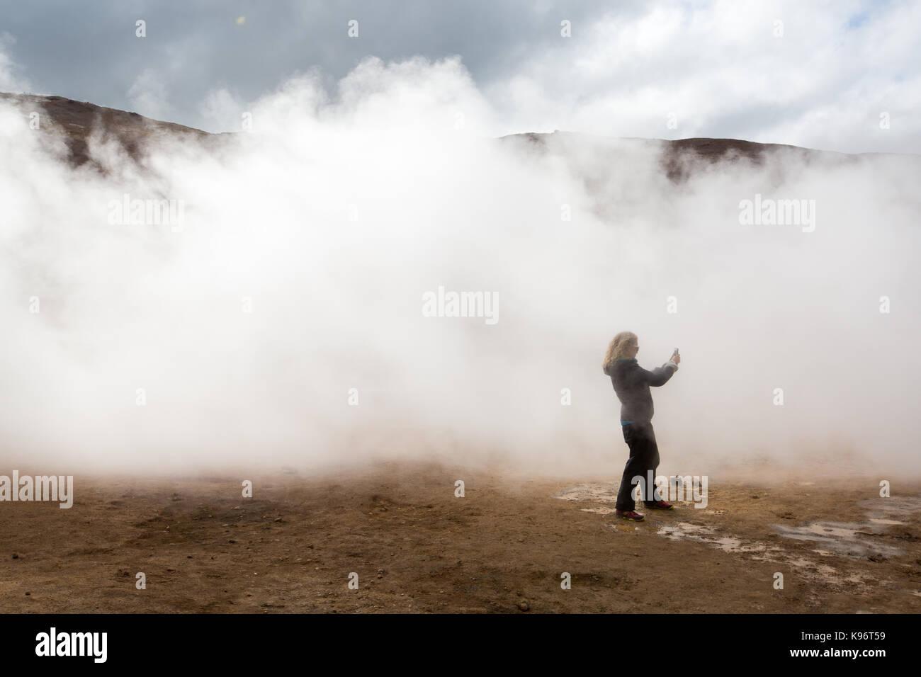Una donna fotografie tra il fango per la cottura a vapore pentole area geotermale nei pressi del Lago Myvatn. Immagini Stock
