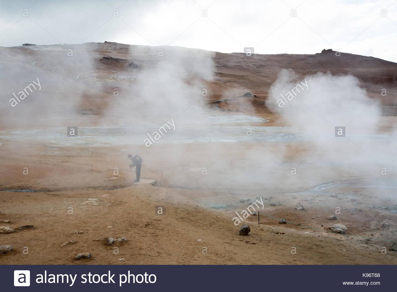 Un uomo guarda le fotografie e il fango per la cottura a vapore pentole area geotermale nei pressi del Lago Myvatn. Immagini Stock