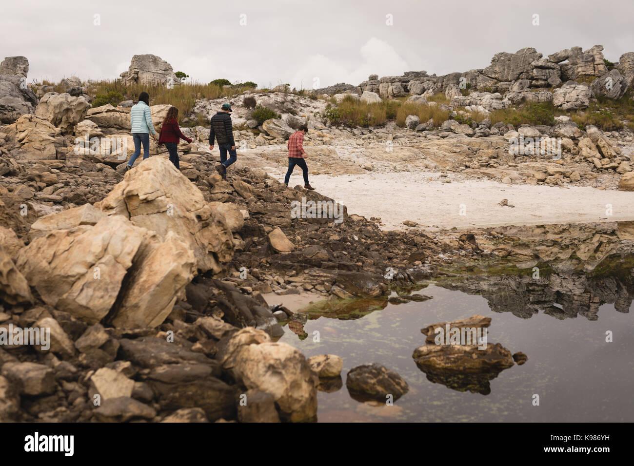 Gruppo di amici a piedi vicino al lago in una giornata di sole Foto Stock