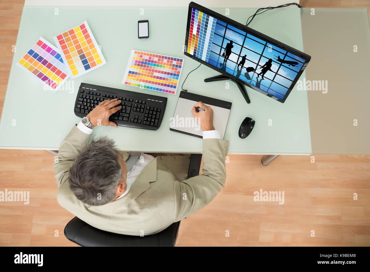 Elevato angolo di visione dell uomo d affari con tavoletta grafica in ufficio. fotografo possiede il copyright per Foto Stock