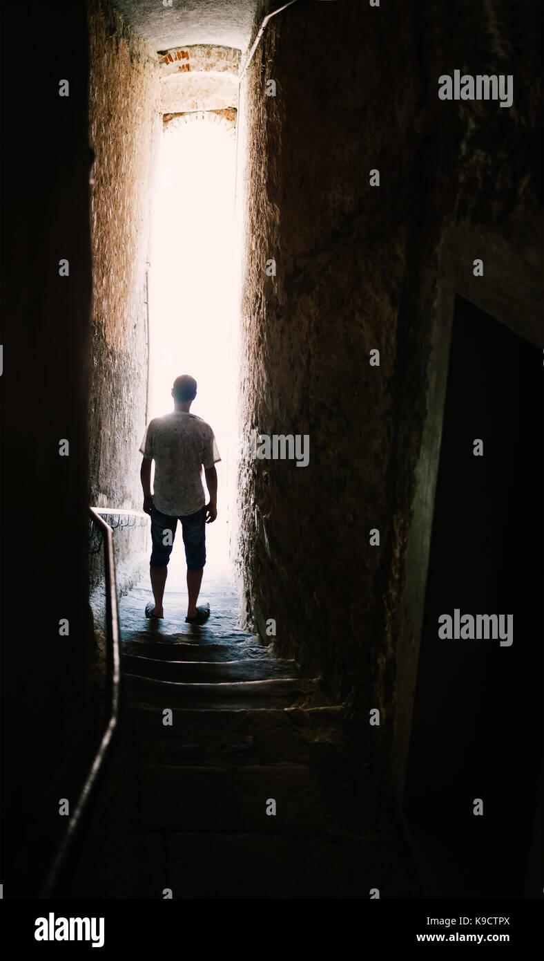 Silhouette uomo su scale nella strada stretta. Concetto misterioso Immagini Stock