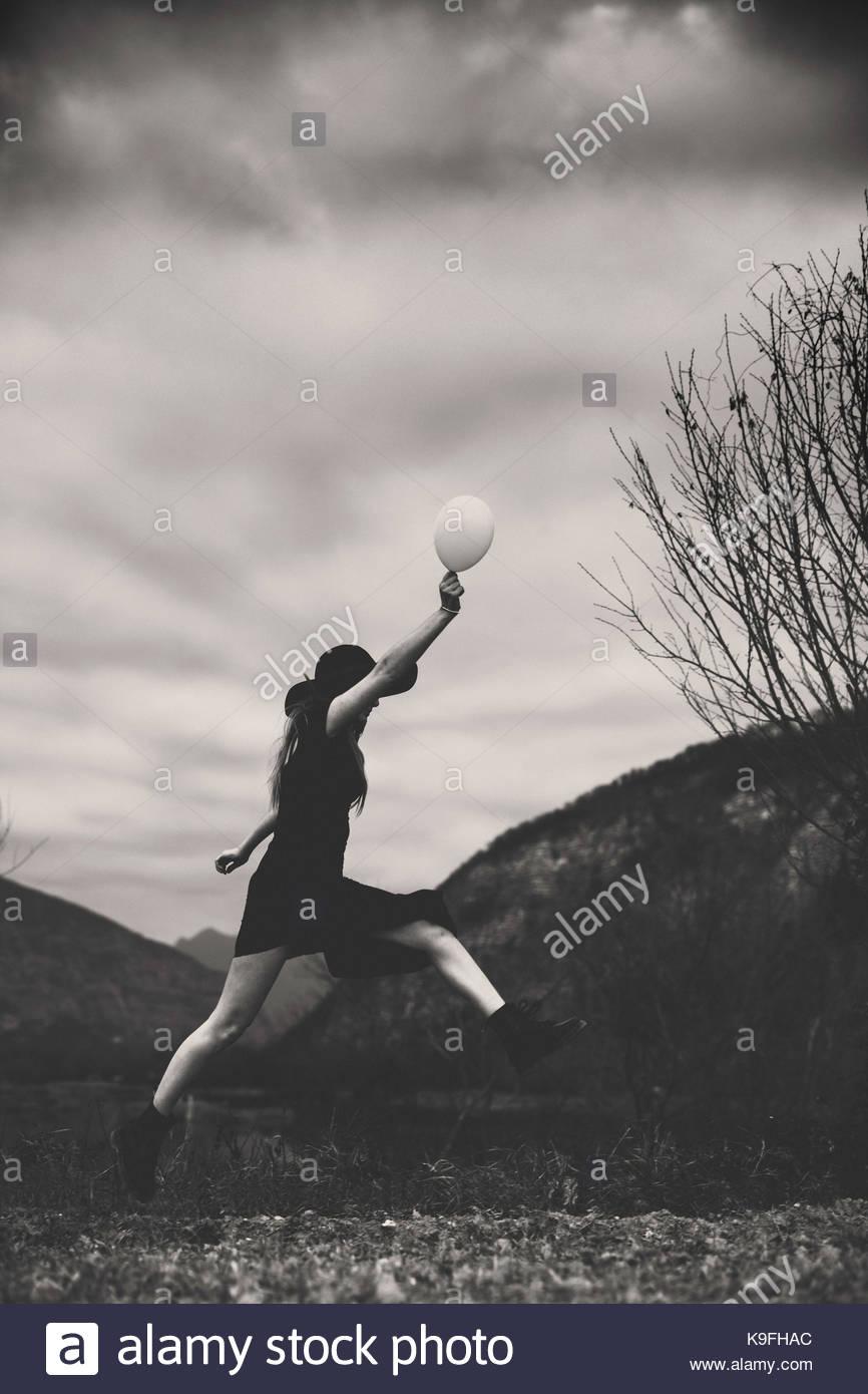 Signora in un campo: salto tenendo un palloncino bianco Immagini Stock