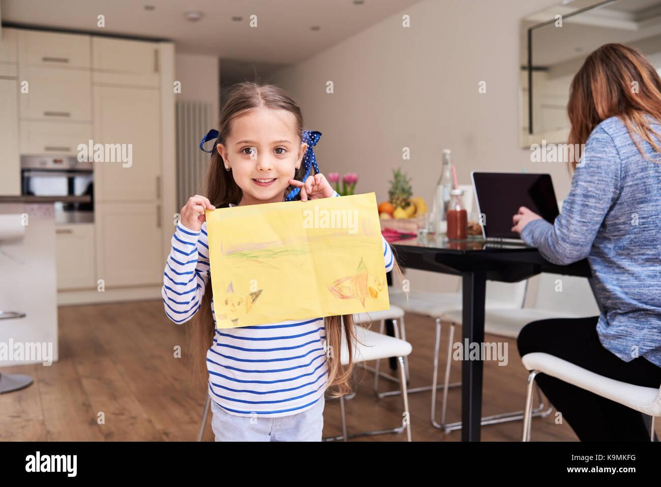 Ritratto di sorridente bambina che mostra il disegno mentre sua madre lavora sul computer portatile in background Immagini Stock