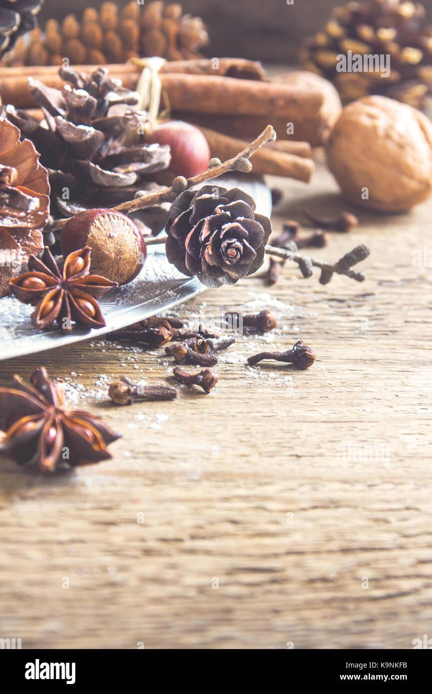 Natale decorazione vintage con bastoncini di cannella e anice stellato, coni, dadi e ornamenti natale su legno rustico Immagini Stock