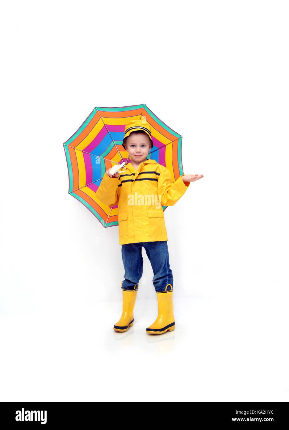 Little Boy controlli per la pioggia mentre vestita di un giallo più lustro e stivali di gomma e hat. Egli è Immagini Stock