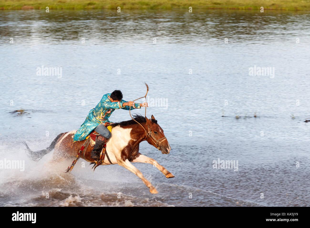 Giovane cavaliere mongolo corse al galoppo completo sul fiume Immagini Stock