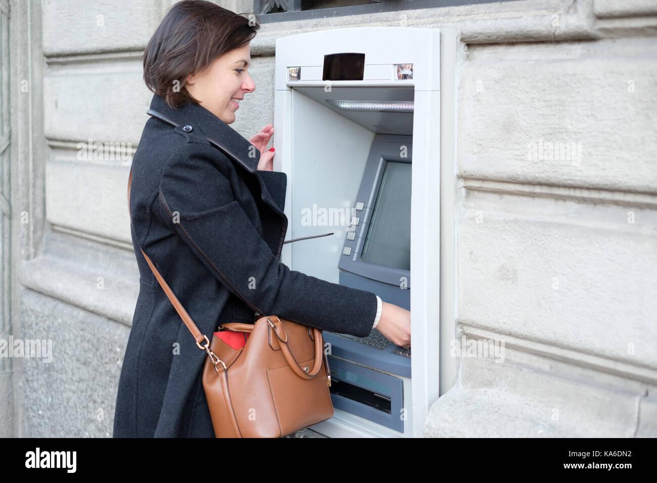Donna che fa una banca il prelievo in un bancomat Immagini Stock