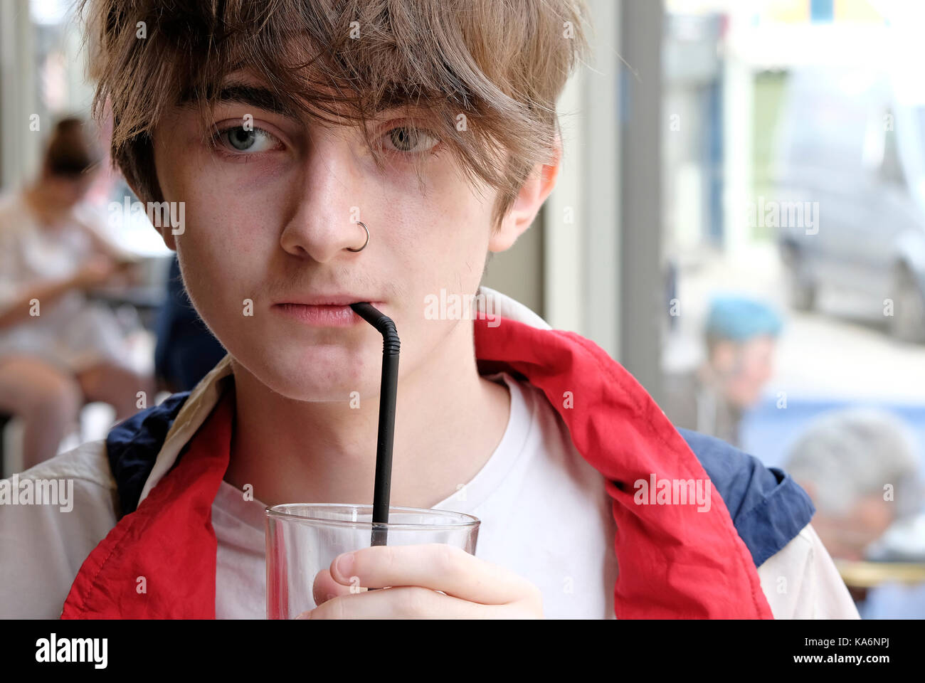Adolescente di bere una bevanda analcolica dal paglia nel cafe interior Immagini Stock