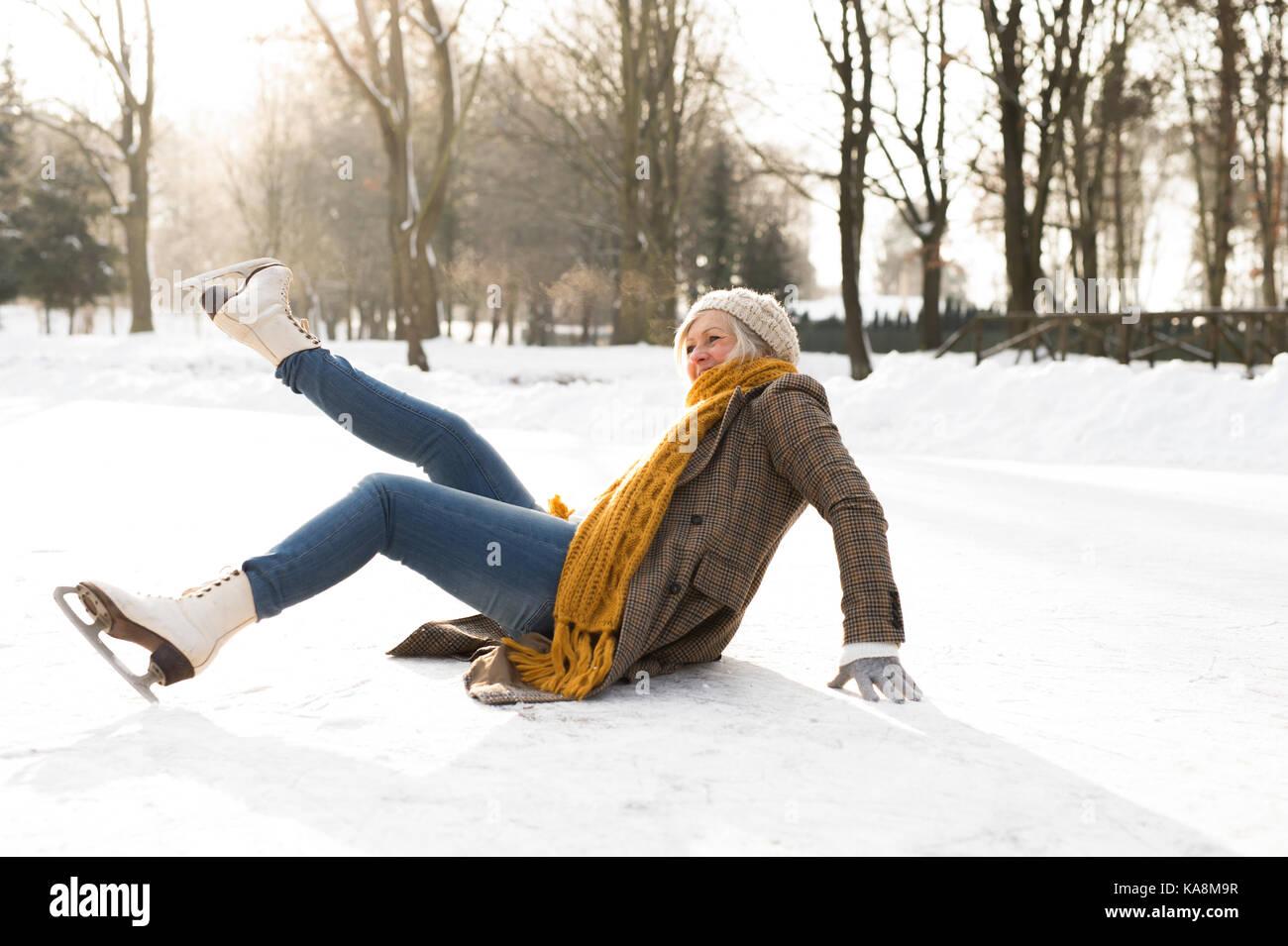 Senior donna sul ghiaccio dopo una caduta. Foto Stock