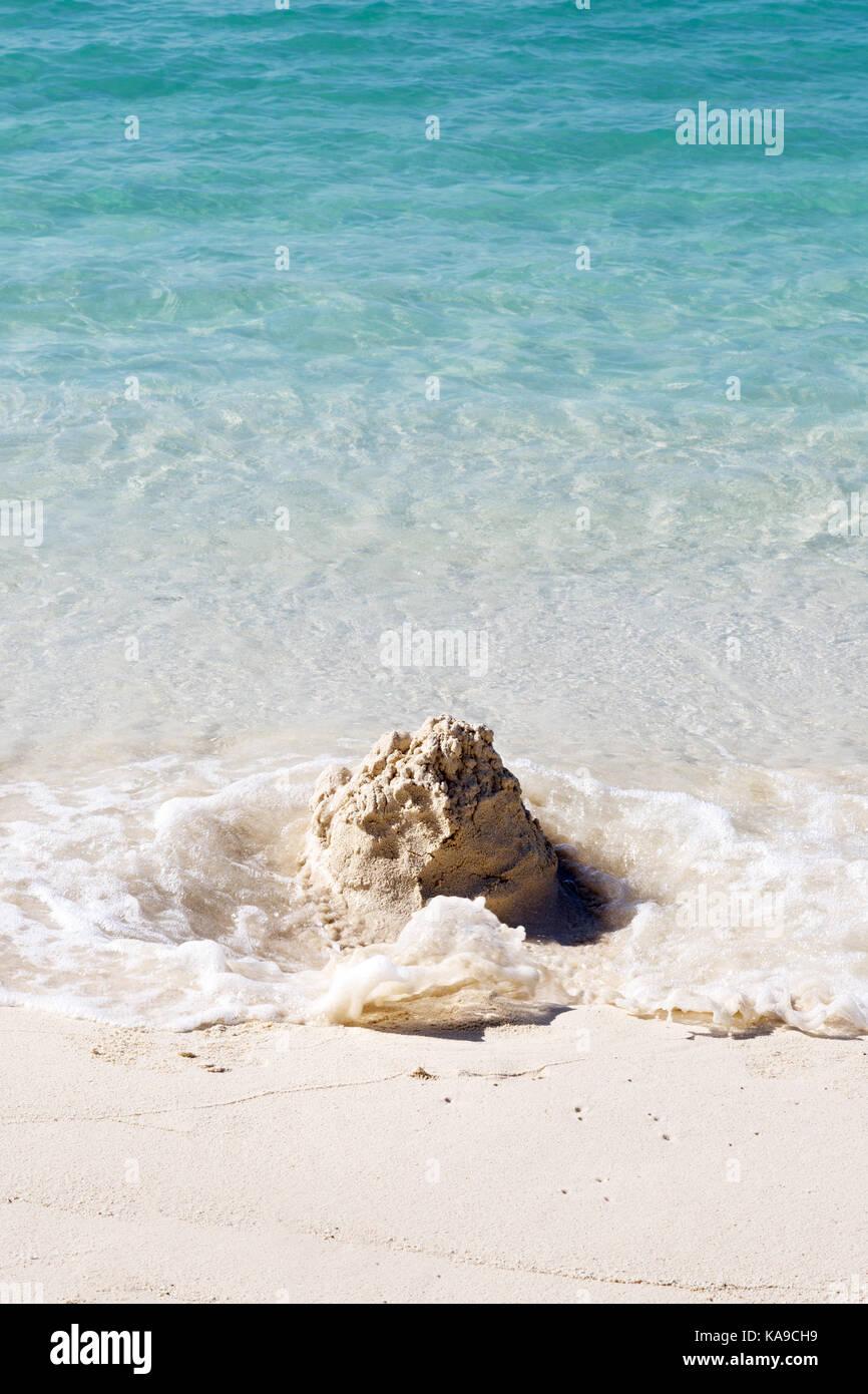 Castelli di Sabbia sulla spiaggia di essere lavati via dalle onde - Concetto di inevitabilità, tempo, temporanei Immagini Stock