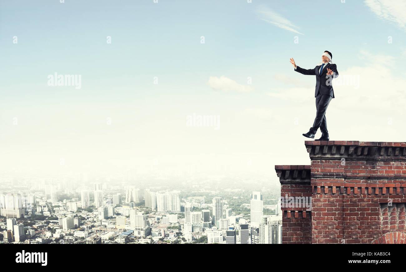 Pericolo e rischio concetto con imprenditore rendendo il passo dal bordo Immagini Stock