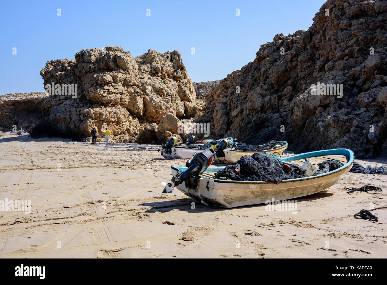 I pescatori disponendo la loro rete sulla spiaggia di Ras Al Jinz oltre ad alcune barche, Oman Immagini Stock