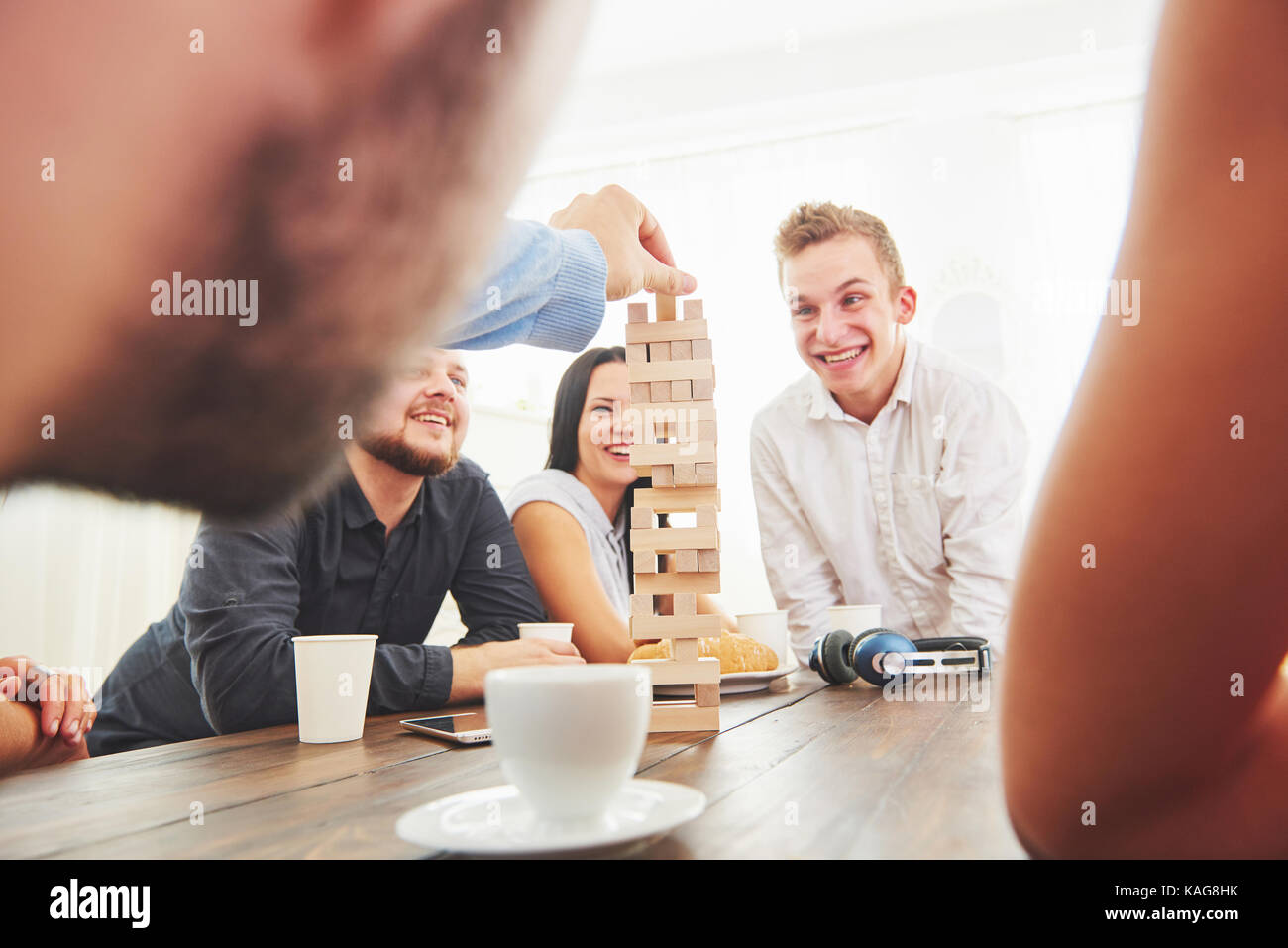 Gruppo di amici creativi seduti ad un tavolo di legno. persone avendo divertimento durante la riproduzione di un Immagini Stock
