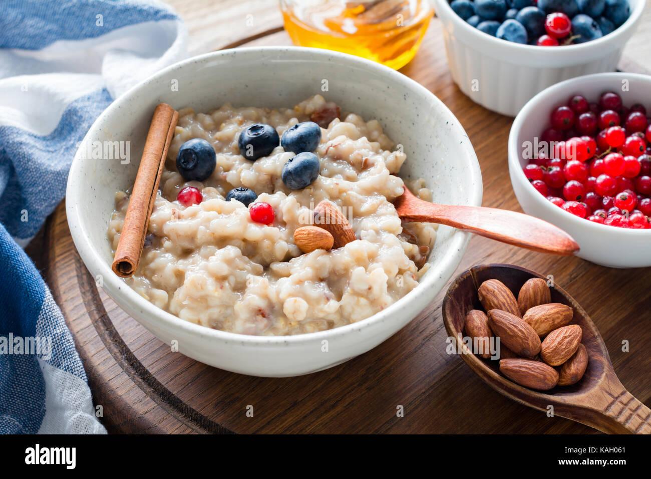 Farina di avena porridge con mirtilli, mandorle e uva secca di Corinto nella ciotola. una sana prima colazione, Immagini Stock