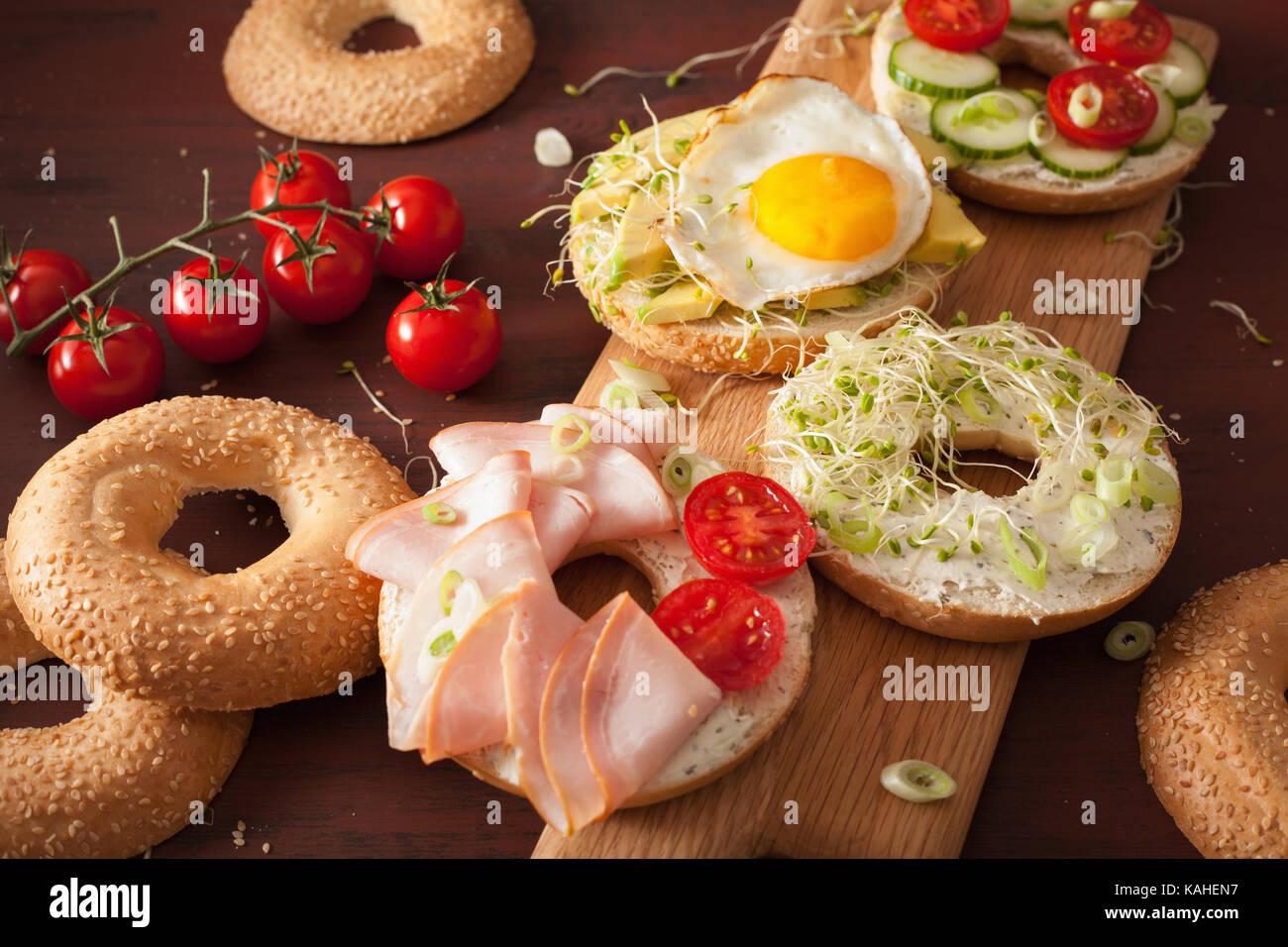 Varietà di panini su bagel: uovo, avocado, prosciutto, pomodoro, formaggio a pasta morbida, di germogli alfalfa Immagini Stock