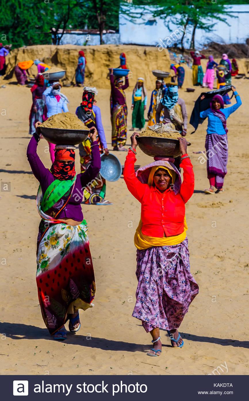 Rajasthani donne in colori luminosi di lavoro (portando lo sporco) in un progetto di costruzione lungo la strada Immagini Stock