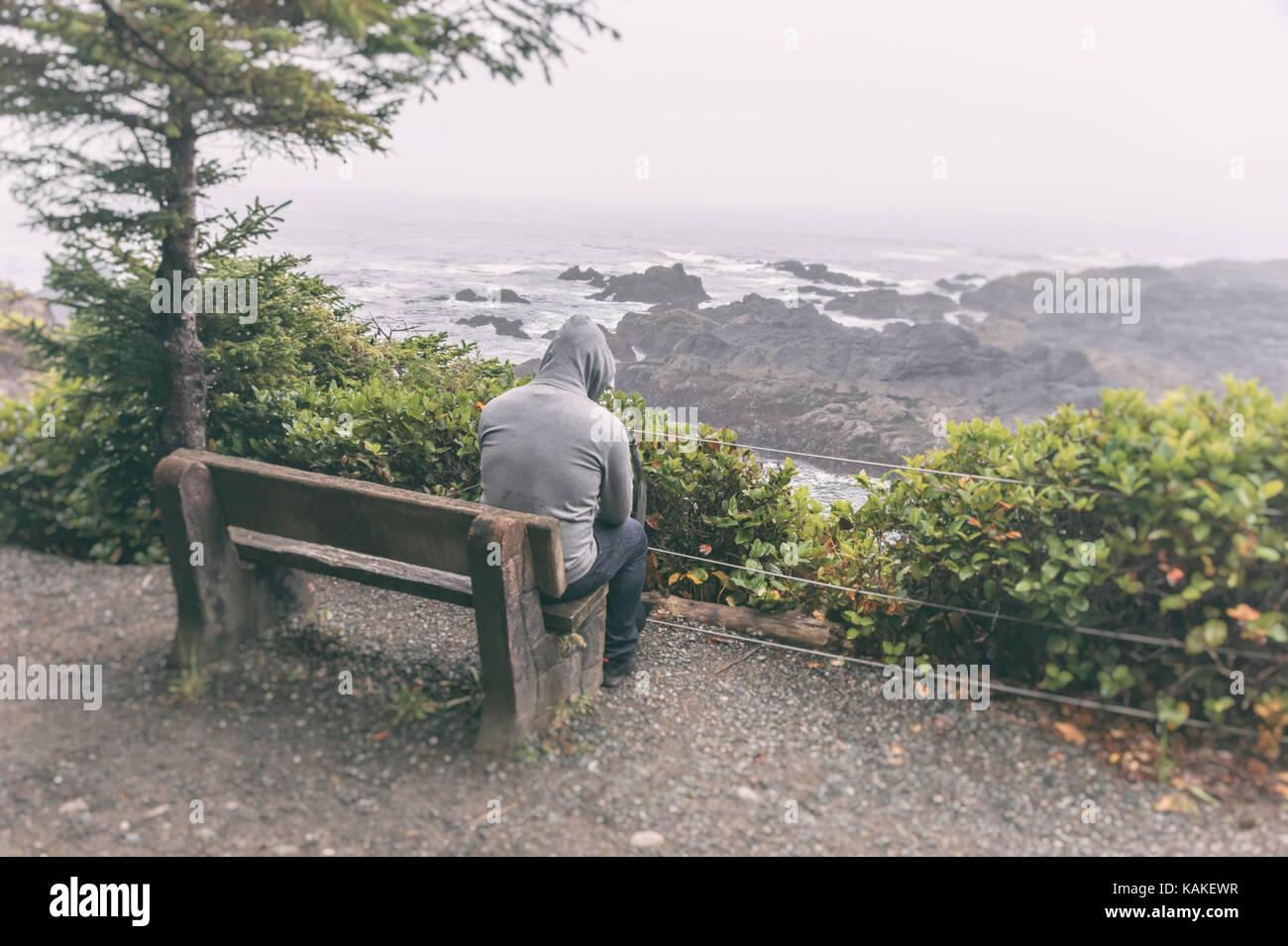 Triste e solitaria uomo seduto su un banco di lavoro affacciato sul mare sull'isola di Vancouver Immagini Stock