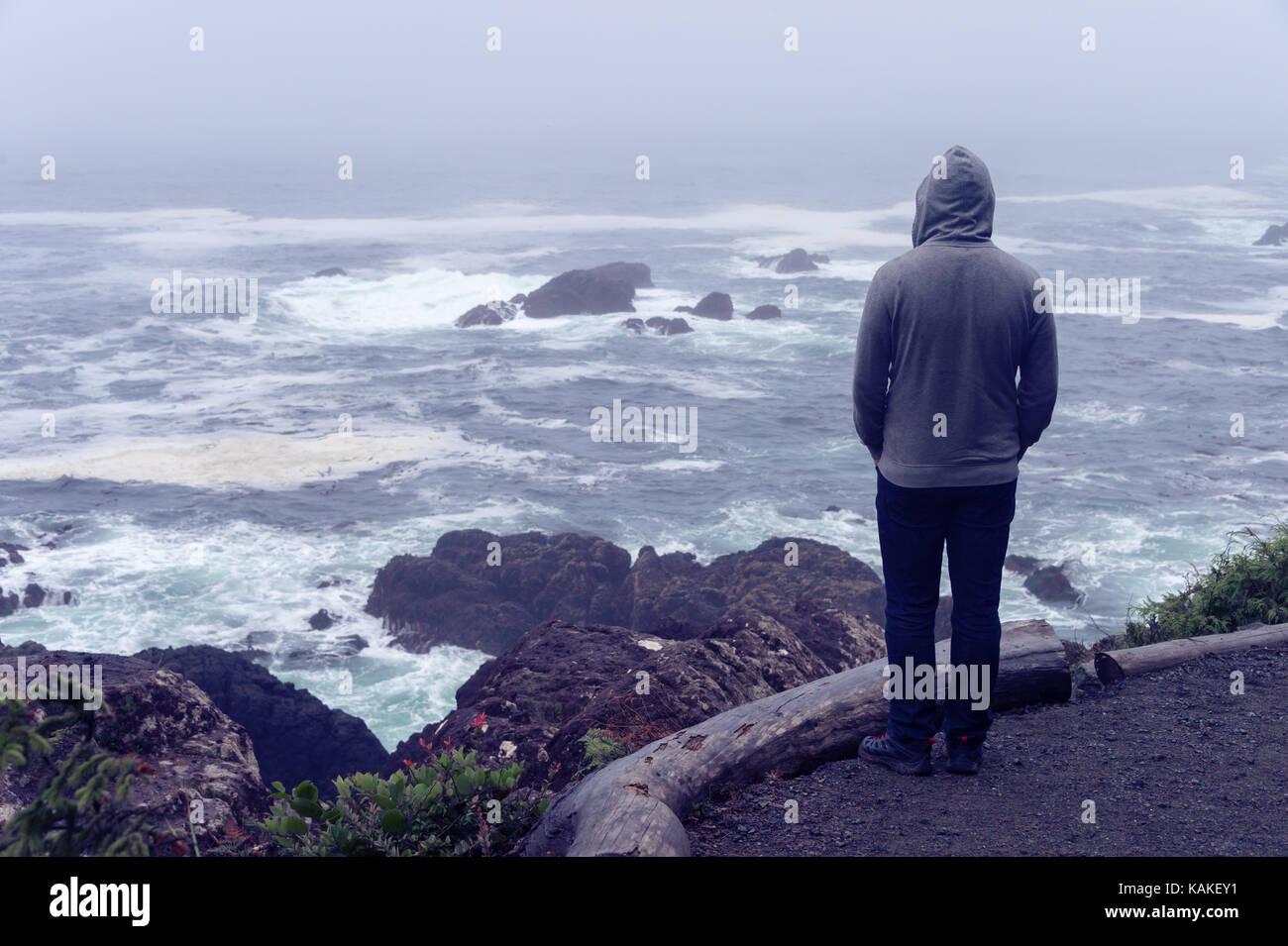 Lonely Man standing di fronte all'oceano pacifico e guardando il mare tempestoso sull'isola di Vancouver. Foto Stock