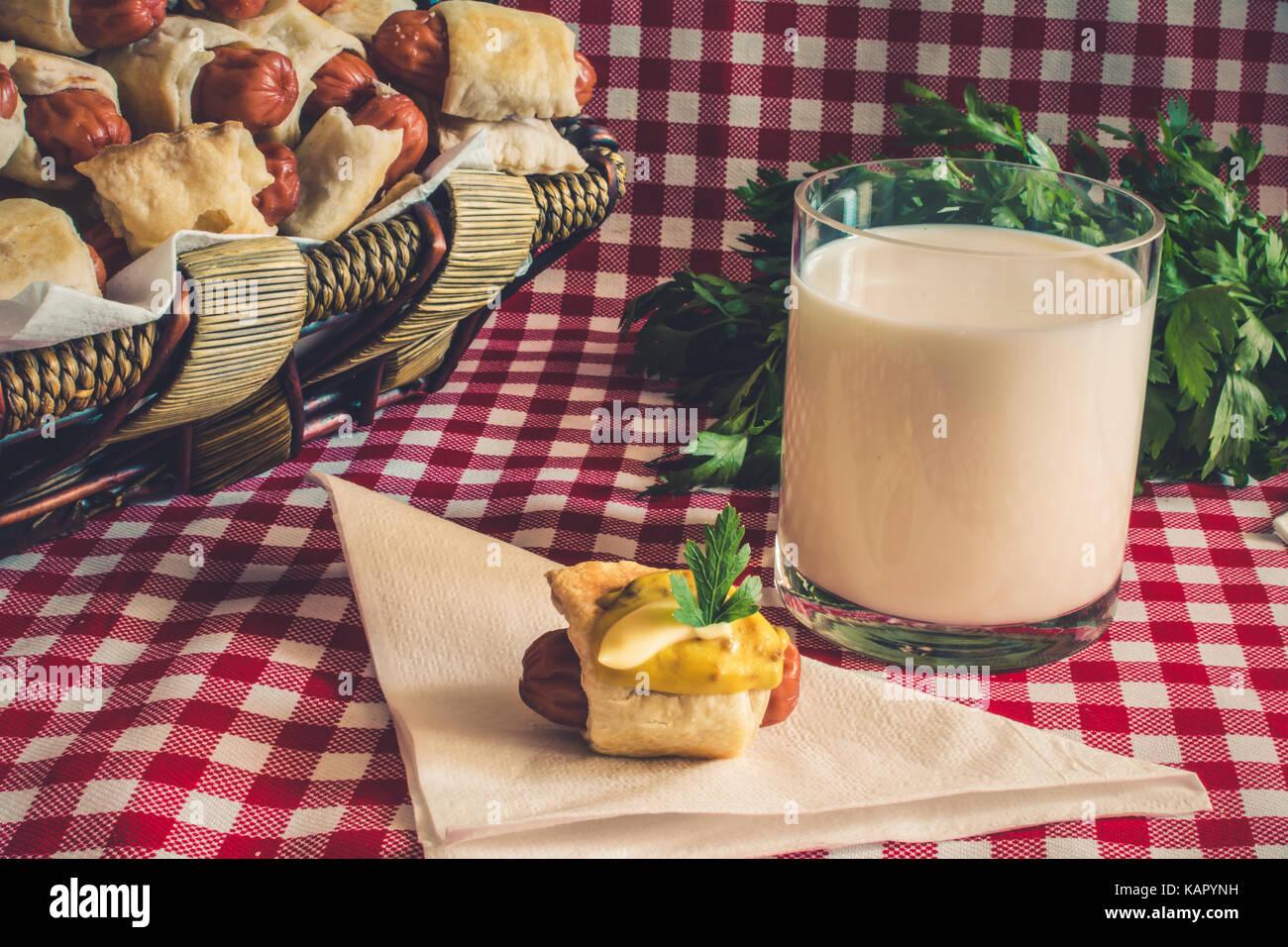 Cesto in Vimini con artigiano mini hot dogs (salsiccia nell'impasto) con salsiccia su un tovagliolo coperte di senape, Foto Stock