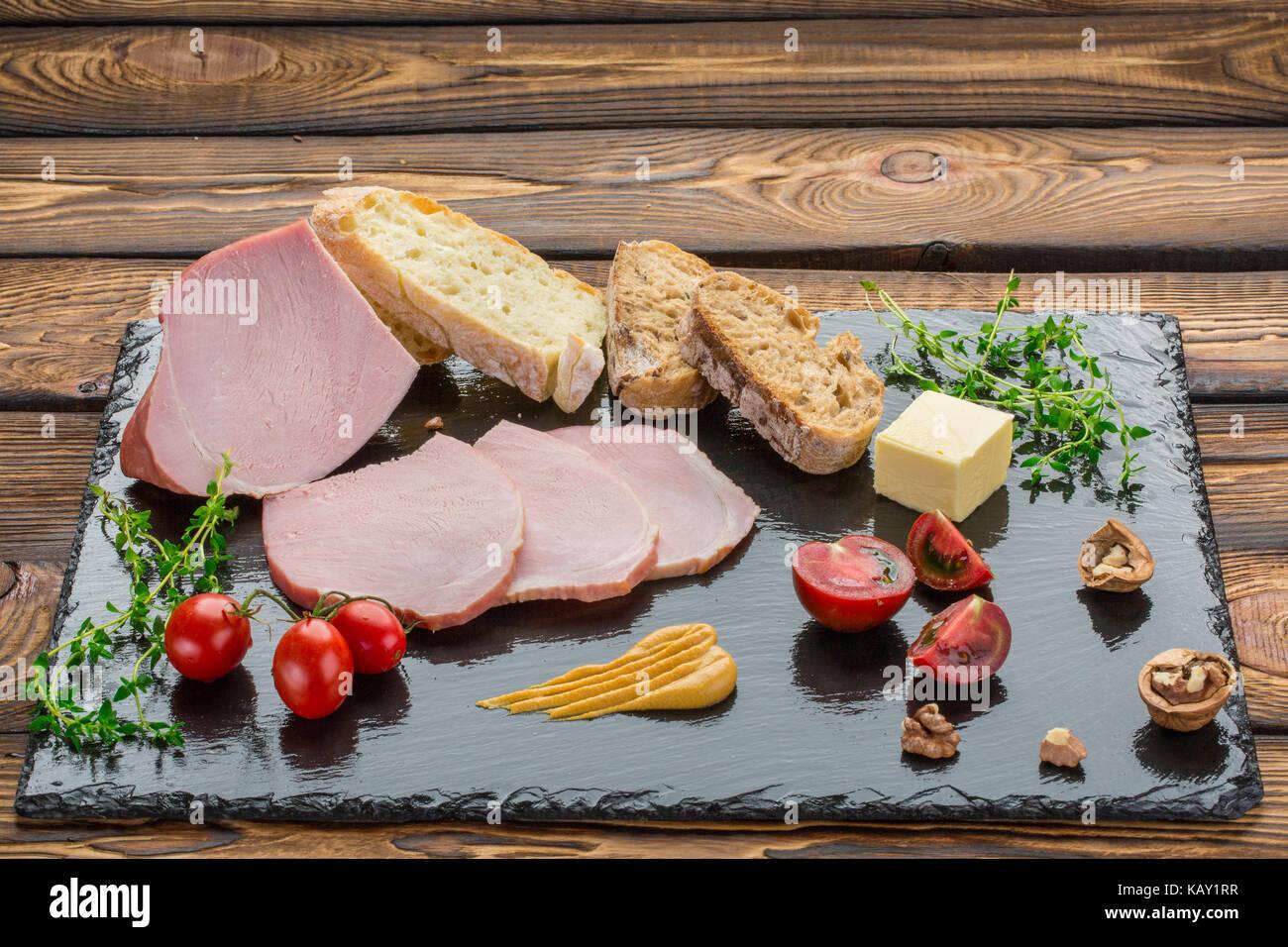 Pezzi di cold-bollite, pane, burro, pomodori, erbe, noci, la senape. Ingredienti per la prima colazione sulla pietra Foto Stock