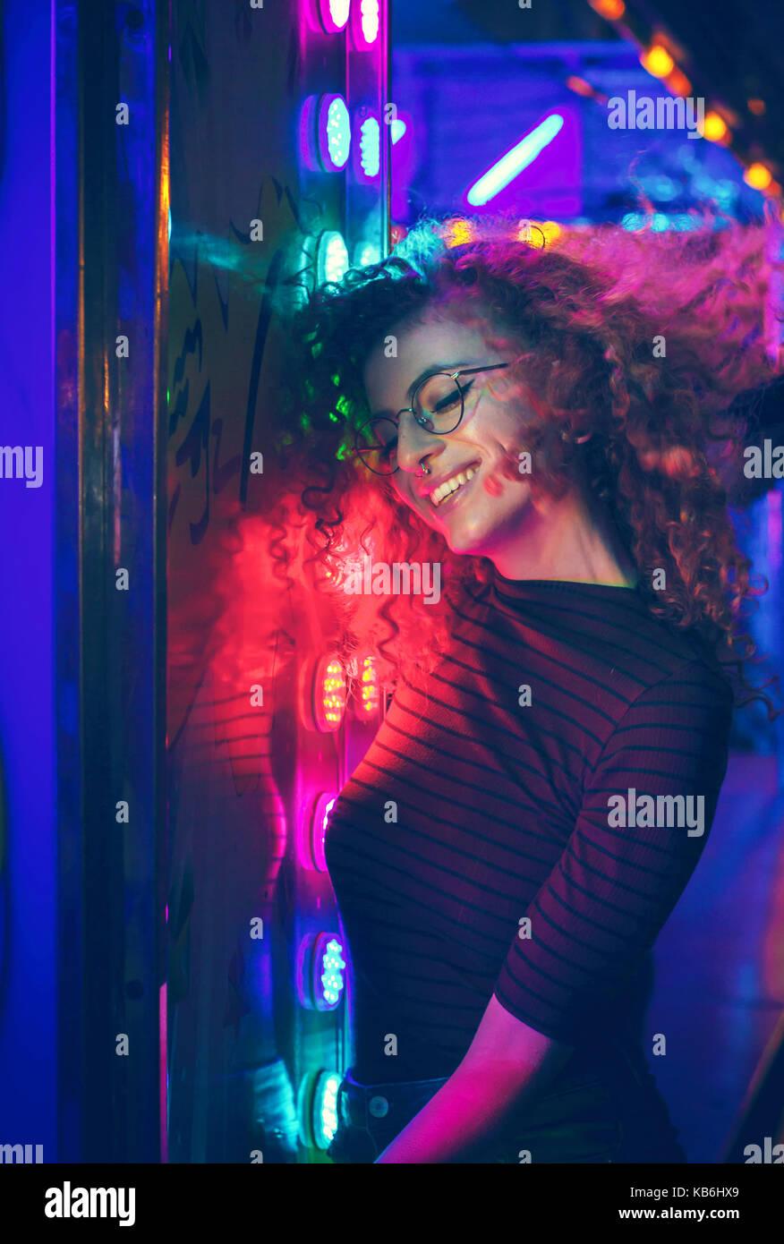 Ritratto di una giovane donna di notte illuminato con luci di colore Immagini Stock