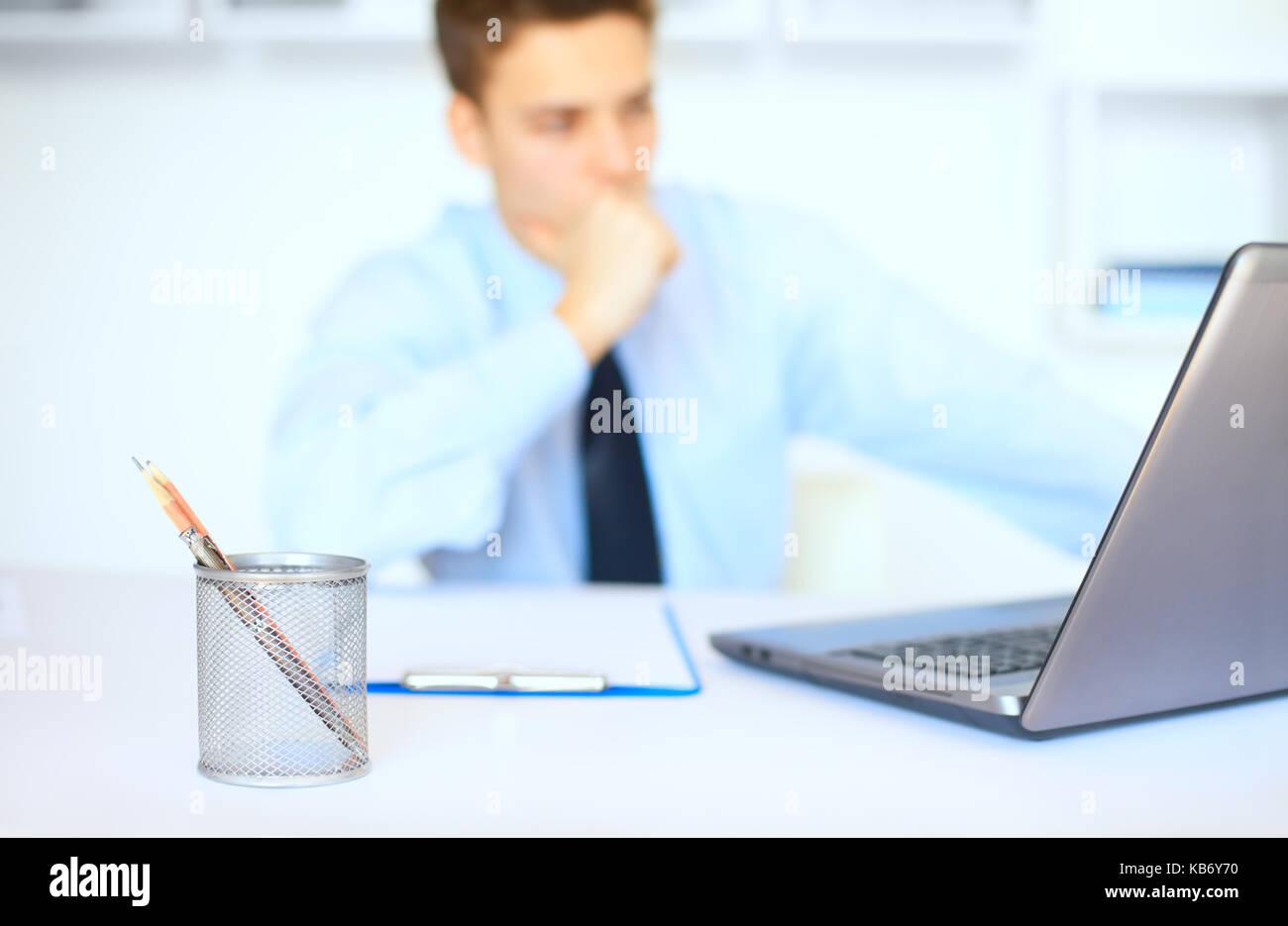 Ritratto di giovane imprenditore pensieroso al suo luogo di lavoro in ufficio luminoso. focus sul Bicchiere portapenne Immagini Stock