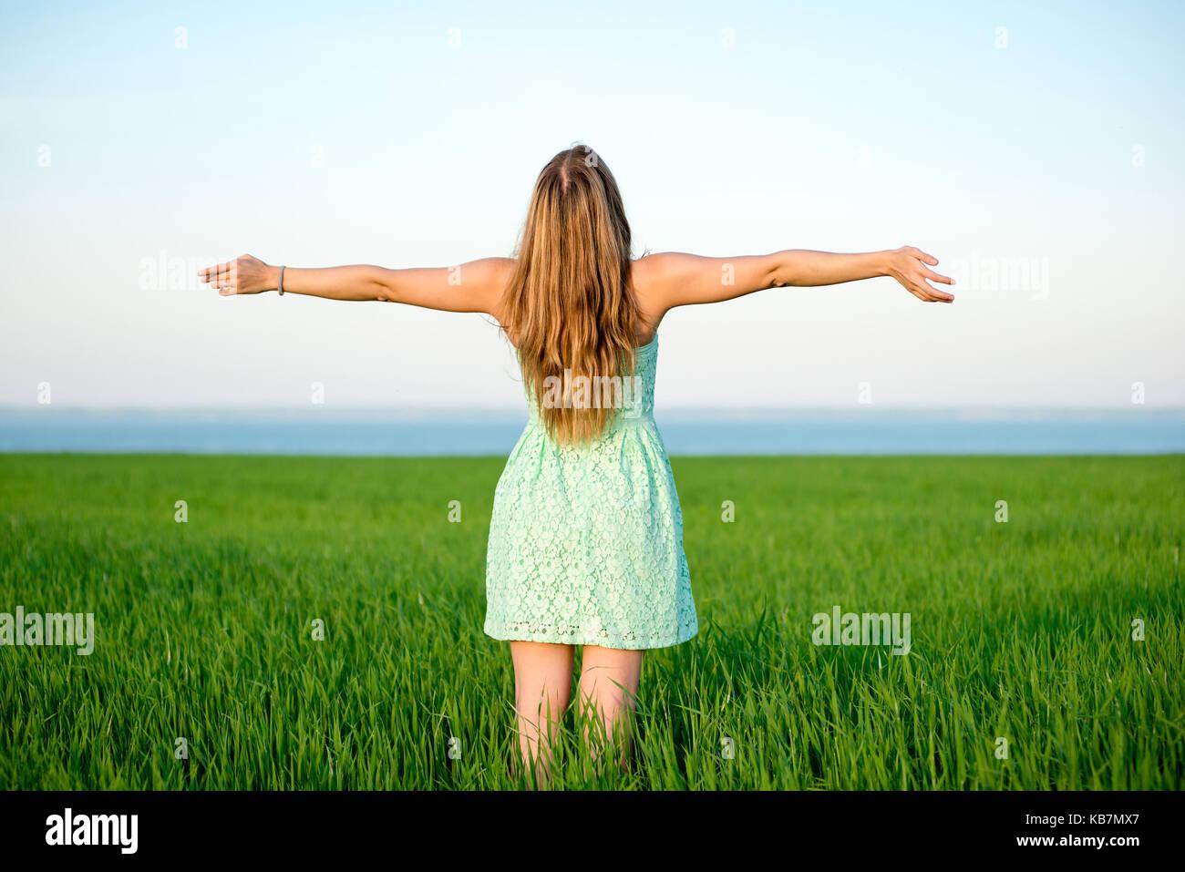 La felicità della donna soggiorno all'aperto sotto la luce del sole del tramonto Immagini Stock