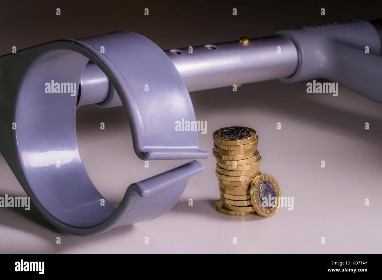 Una stampella e nuovo sterling pound monete. Concetto di legame tra incapacità e Regno Unito sterline, come Immagini Stock