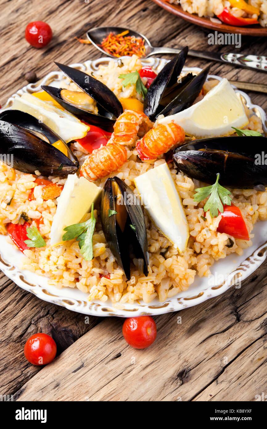 Tradizionale paella vegetale con frutti di mare su sfondo di legno Foto Stock