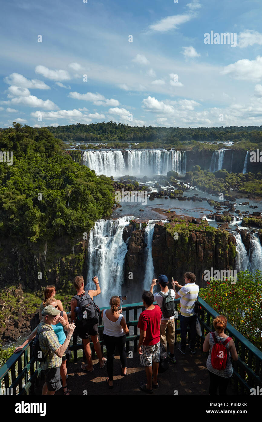 Turisti sulla piattaforma di osservazione sul lato brasiliano delle Cascate di Iguazu, guardando il lato argentino, Sud America Foto Stock