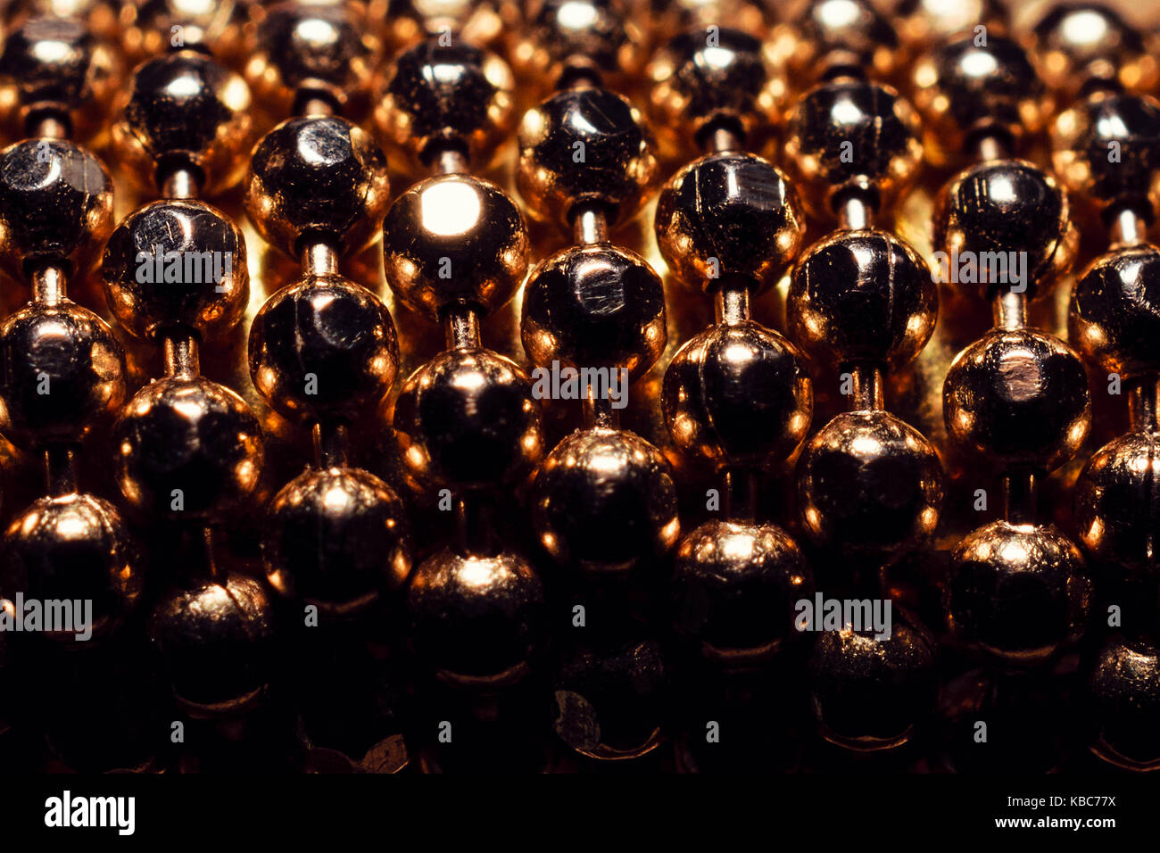 Extreme close-up di sfere d'oro dal bracciale Foto Stock