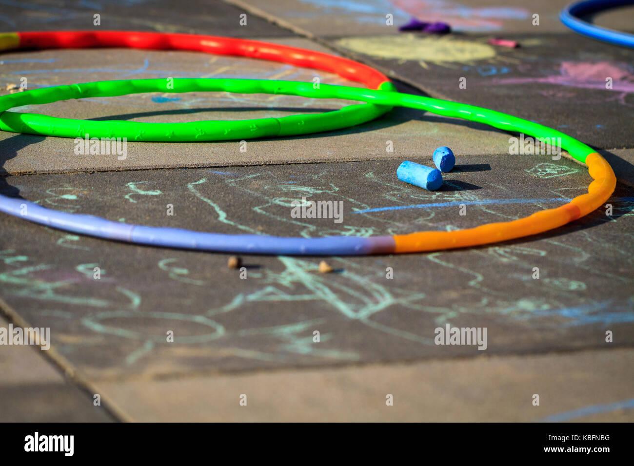 Gesso colorato e hula hoops giaceva sul parco giochi. Immagini Stock