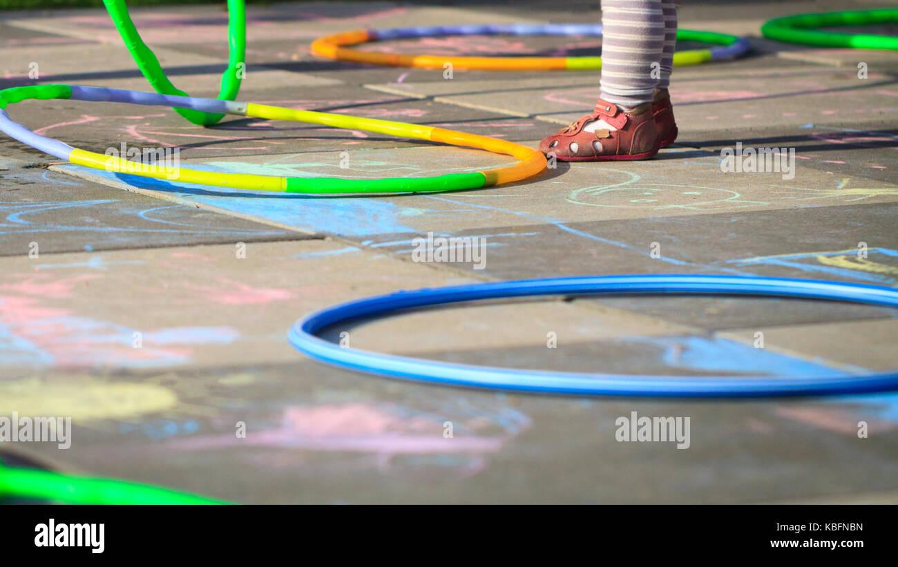 Piccola ragazza giocare hula hoops sul parco giochi graffiato con Chalk. Immagini Stock