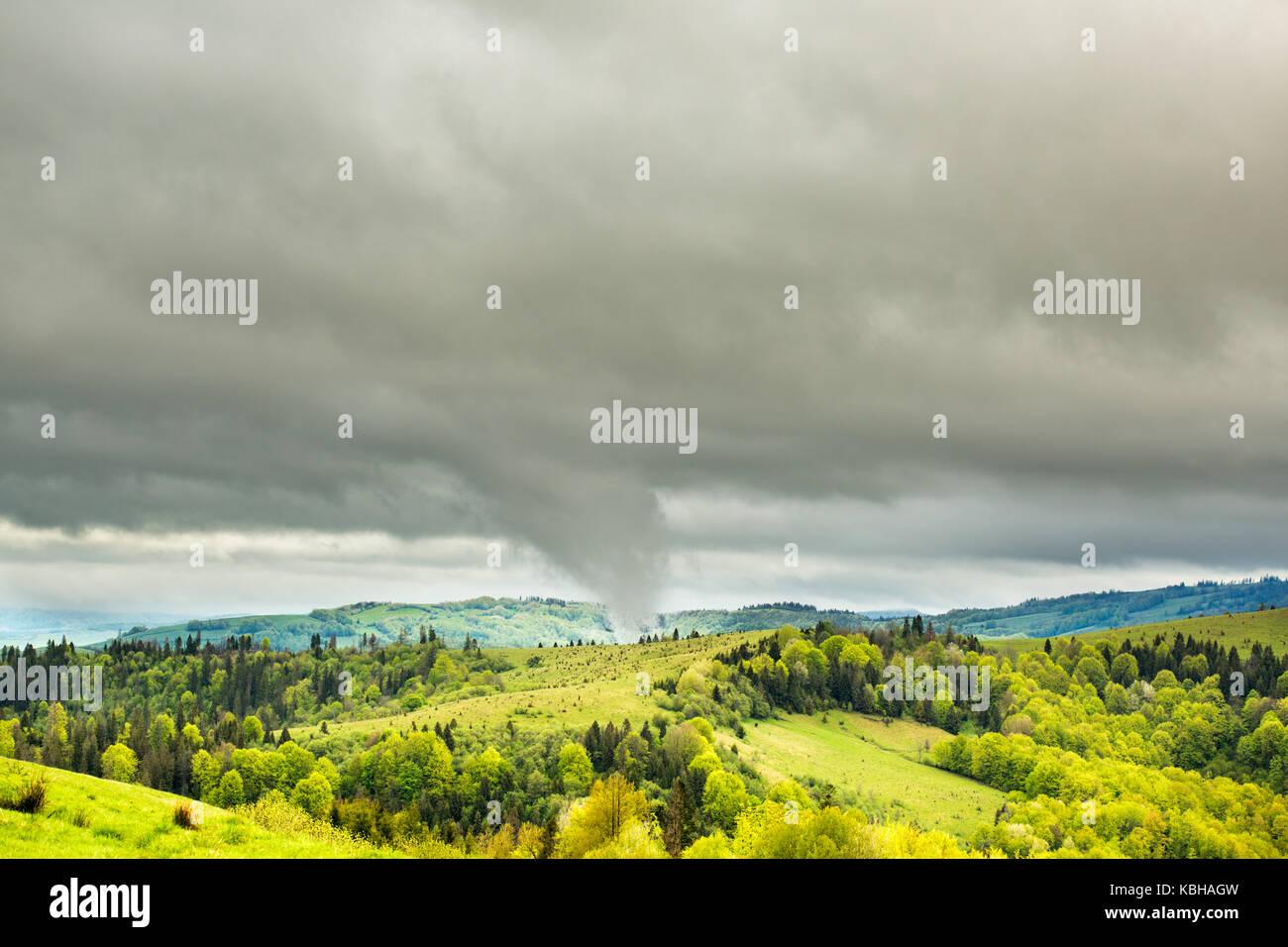 Tornado punta tocca montagna. piccola porzione di prato verde e gli alberi sono visti in primo piano. Il maltempo Foto Stock