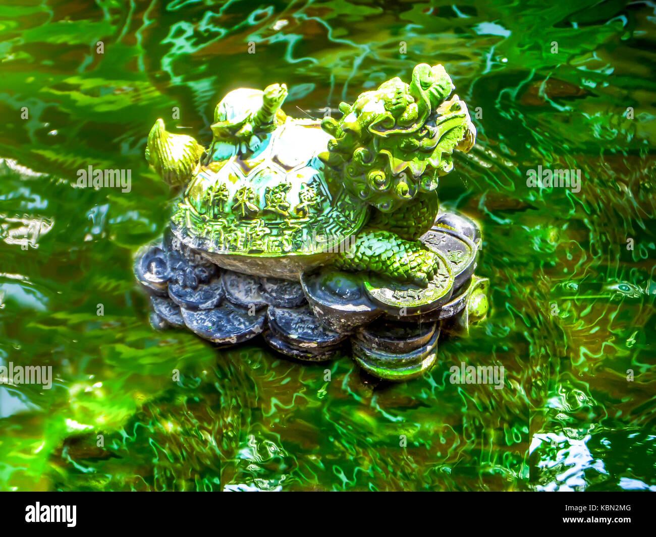 Gold green dragon turtle Pixiu presso la piscina e l'acqua di superficie a specchio, il popolo cinese e alcuni Immagini Stock