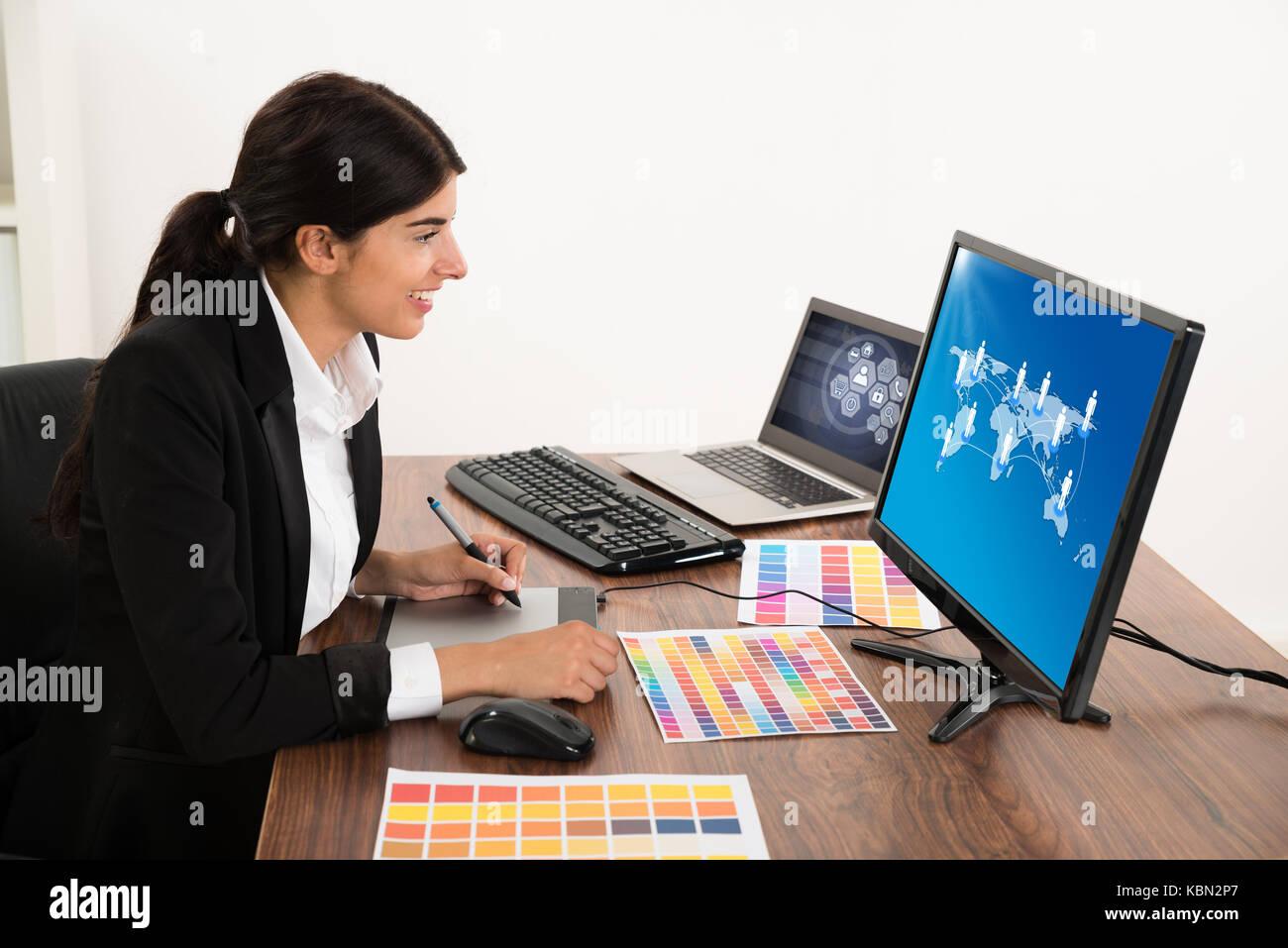 Felice designer femmina guardando il computer mentre si usa tavoletta grafica al desk. fotografo possiede il copyright Immagini Stock