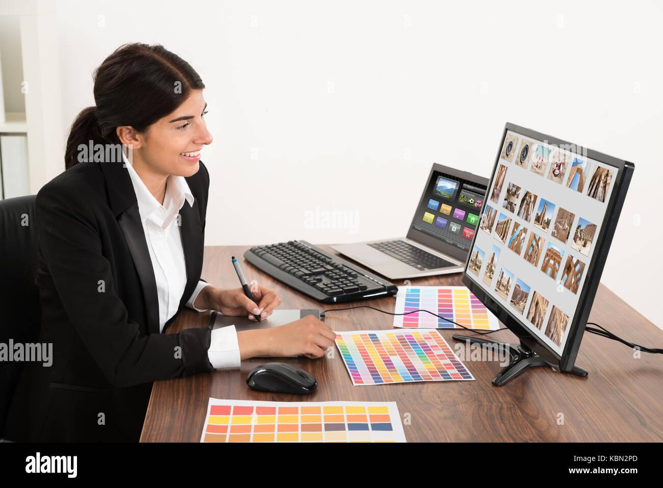Giovane femmina felice graphic designer in ufficio. fotografo possiede il copyright per le immagini sullo schermo Immagini Stock