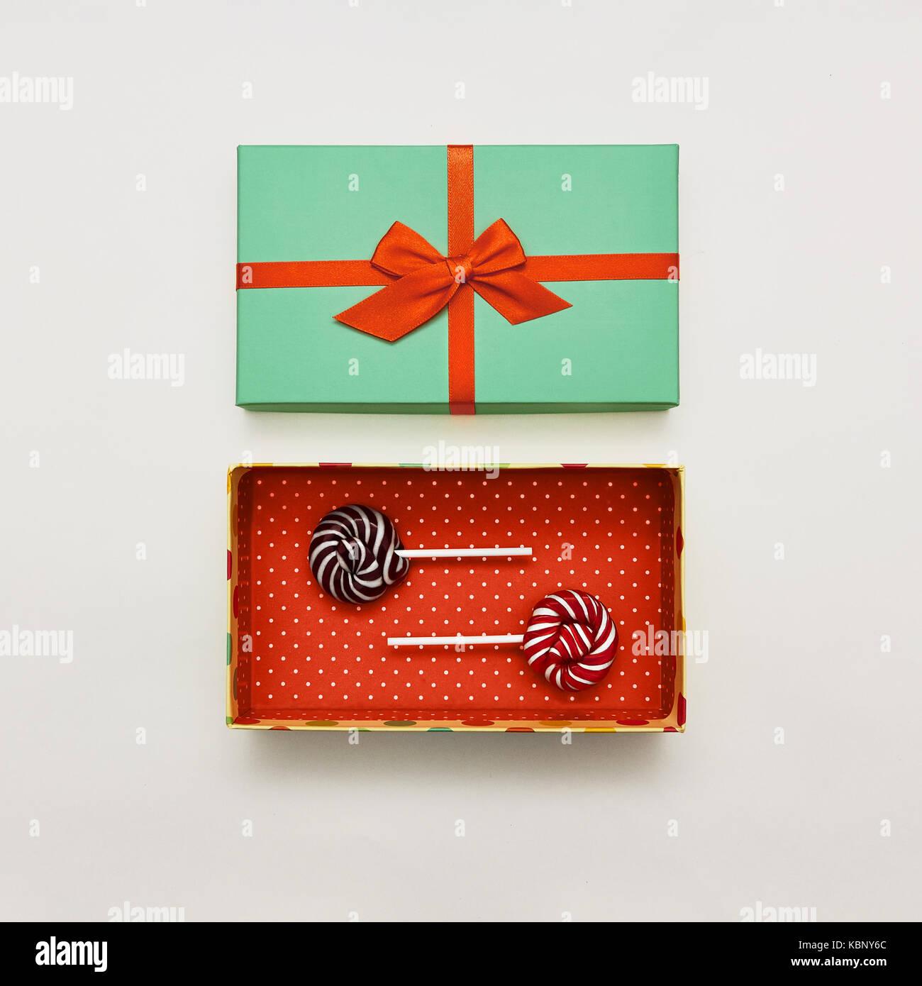 Lecca lecca laici piatta con sfondo bianco due lecca lecca colorati sono giacenti in confezione regalo rossa con Immagini Stock