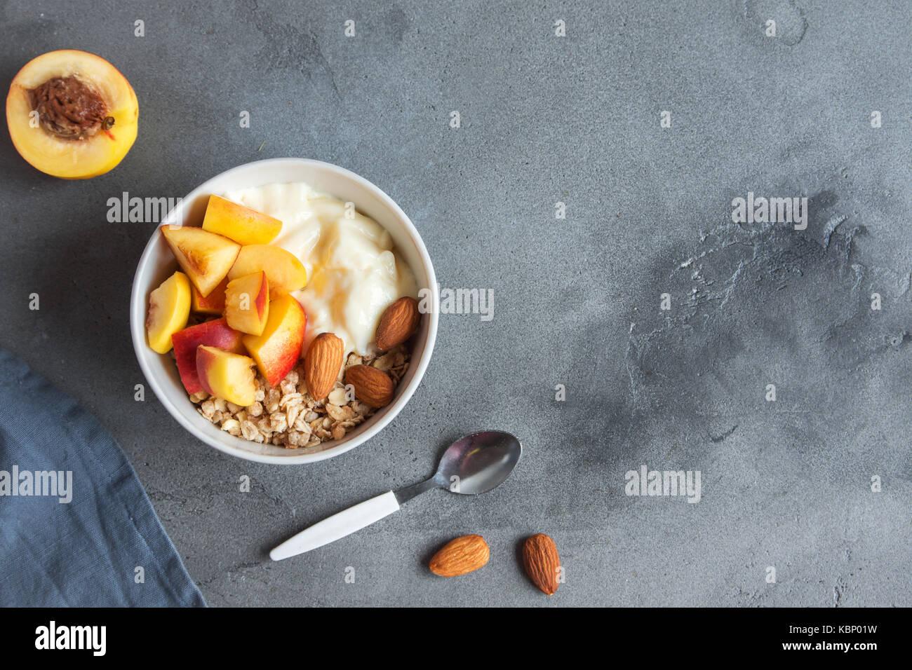 In casa i fiocchi d'avena muesli con yogurt e pesche in un recipiente per una sana prima colazione. a base di Immagini Stock