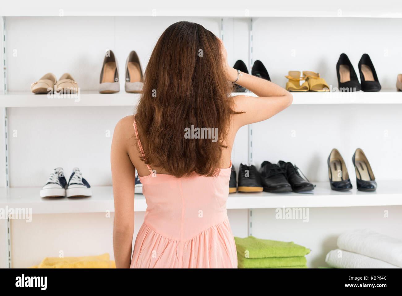 Vista posteriore del confuso giovane donna guardando le scarpe visualizzati  sugli scaffali in negozio Immagini Stock 1ff34f44be3
