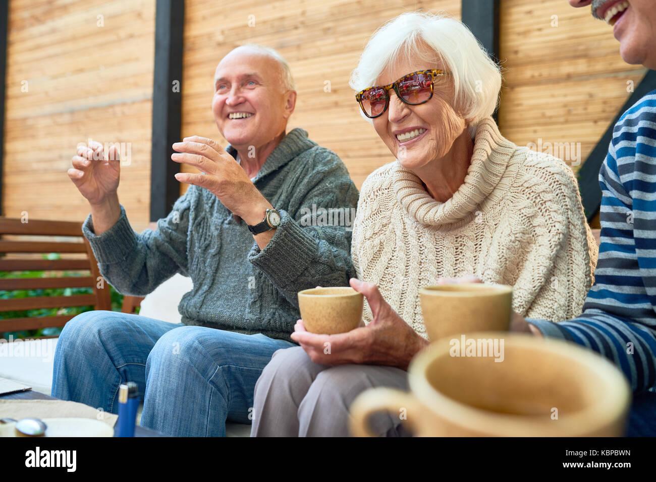 Allegro senior amici radunati insieme al piccolo ed accogliente patio e ricordando storie divertenti dal loro passato, essi indossano Maglioni lavorati a maglia e riscaldamento Foto Stock