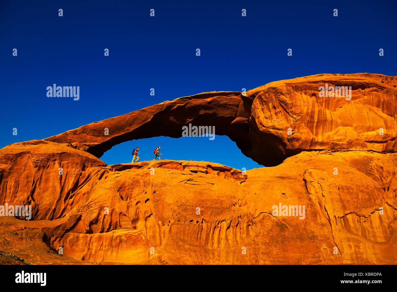 Escursionismo coppia al rock-arch al kharza, Wadi Rum, Giordania, medio oriente Immagini Stock
