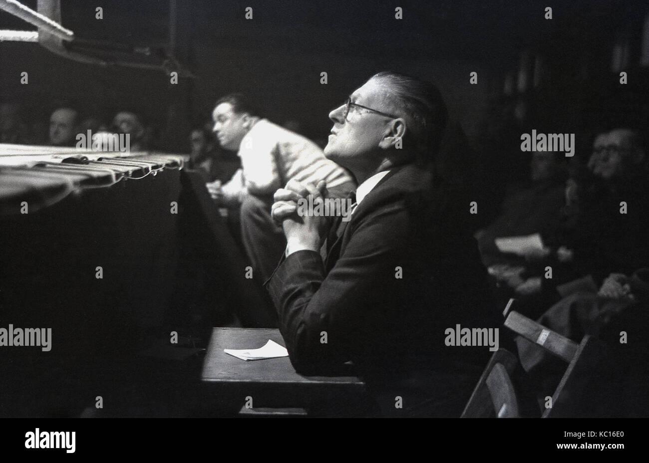 Anni sessanta, storico, giudice maschio siede ringside guardando l'azione ad un incontro di pugilato, Inghilterra, Immagini Stock
