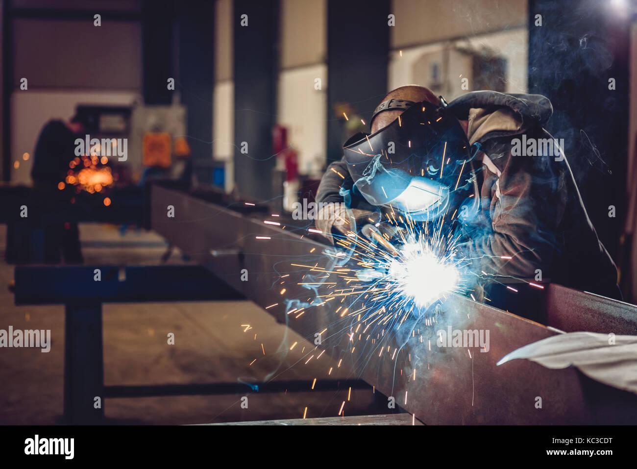 Saldatrice industriale con torcia e casco protettivo nella grande hall di saldatura profili metallici Immagini Stock