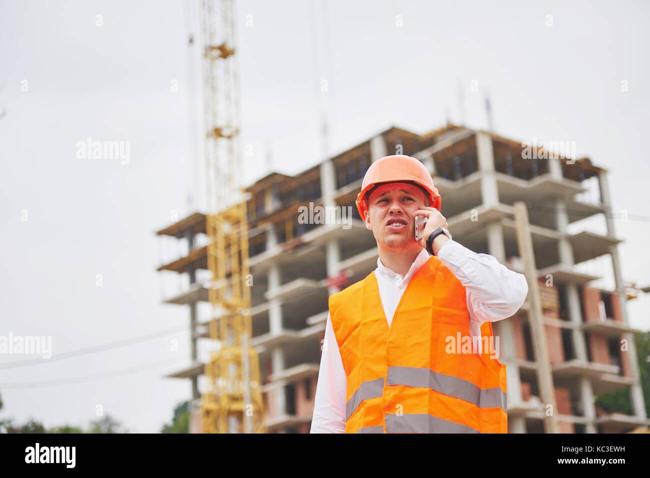 Giovane architetto che indossa un casco di protezione permanente sulla montagna edificio sfondo all'aperto Immagini Stock