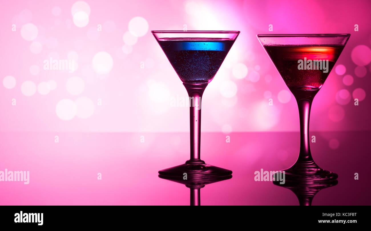 Cocktail colorati sulla sommità riflettente, con sfondo bokeh di fondo Immagini Stock