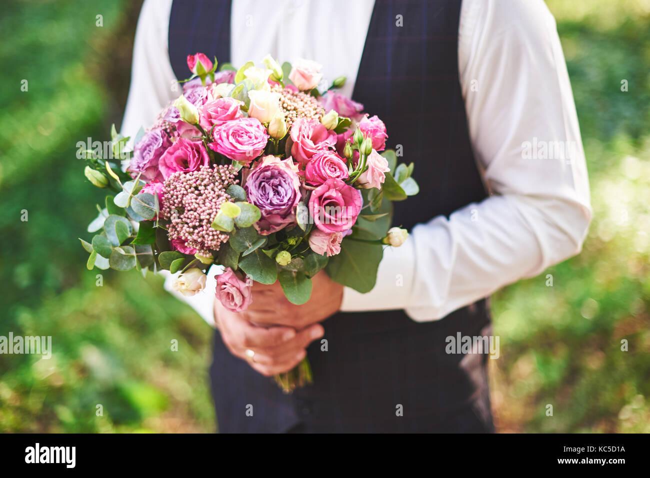 Elegante groom tenendo una gara rosa bouquet di nozze Immagini Stock