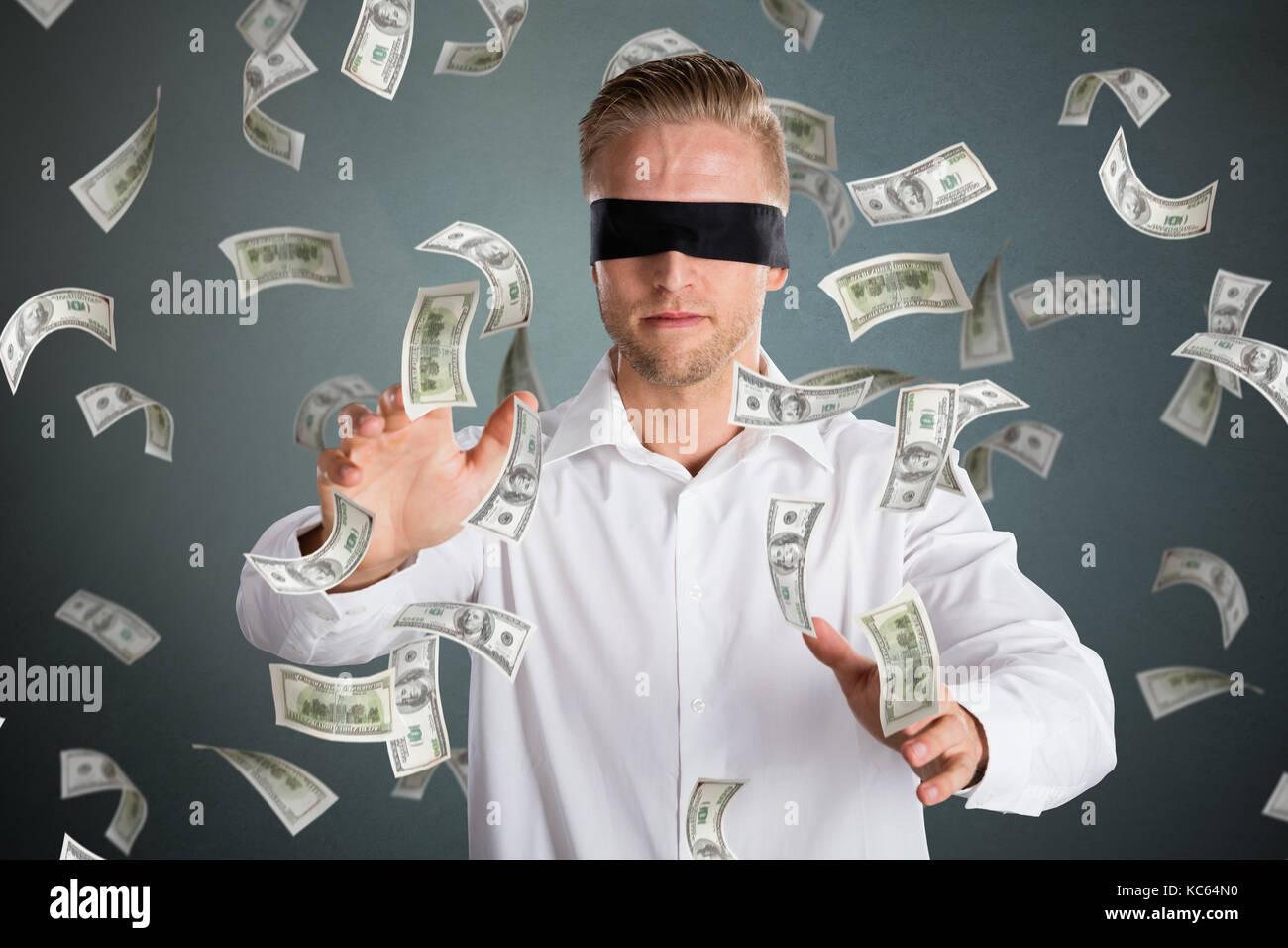Giovane imprenditore bendati con la caduta di denaro contro uno sfondo grigio Immagini Stock